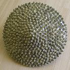 ceramic sculpture of geometric sphere smooth green one side spiked green other side